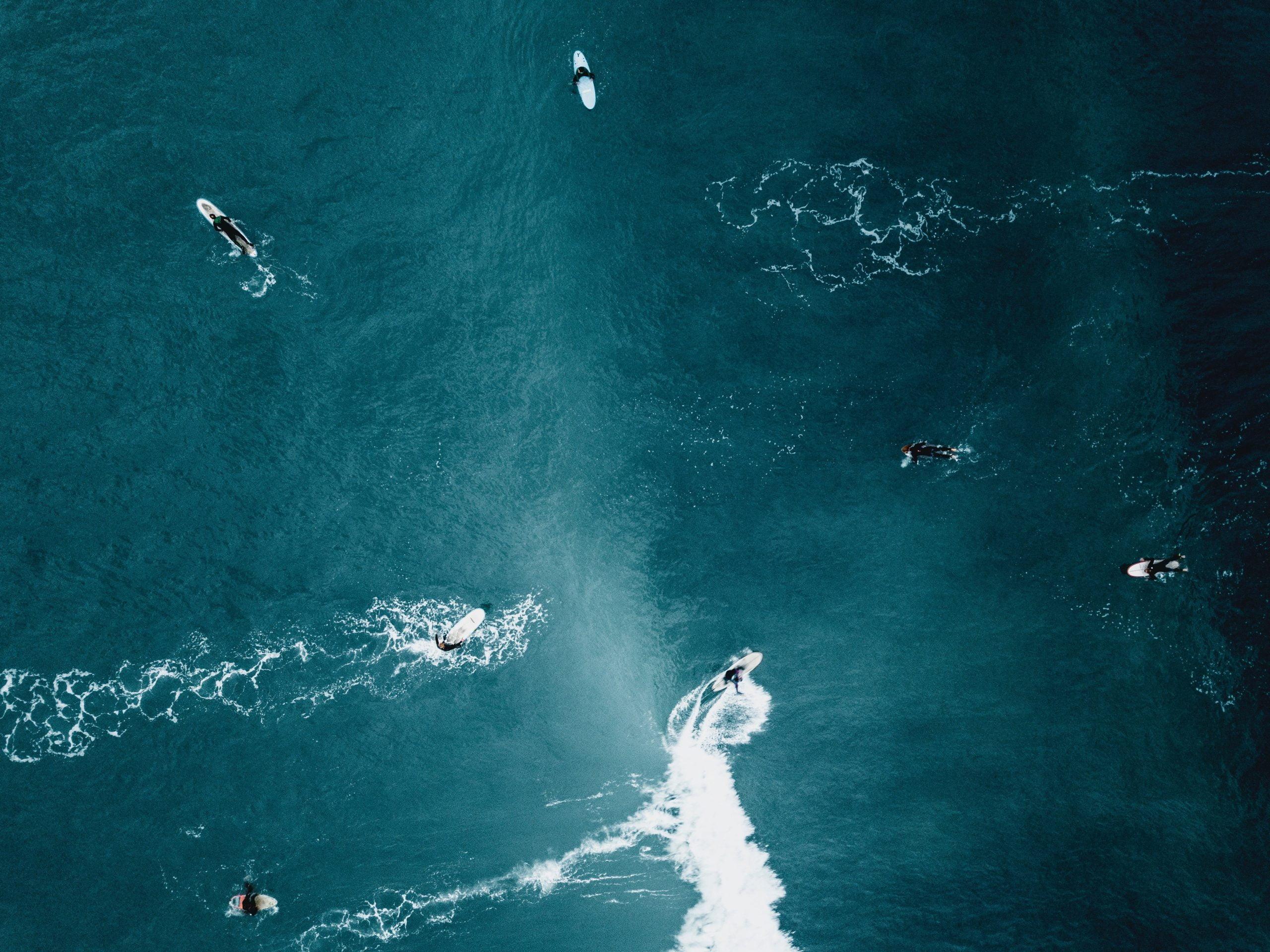 Surfers in helder blauw water